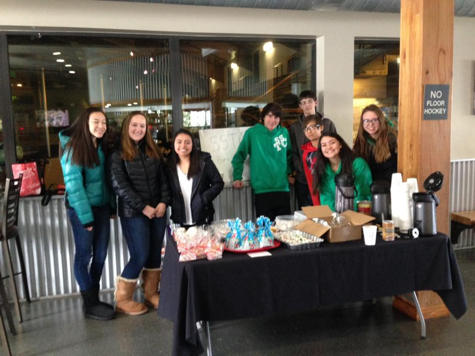 Group of students stands behind table with refreshments at Ice Skating Rink